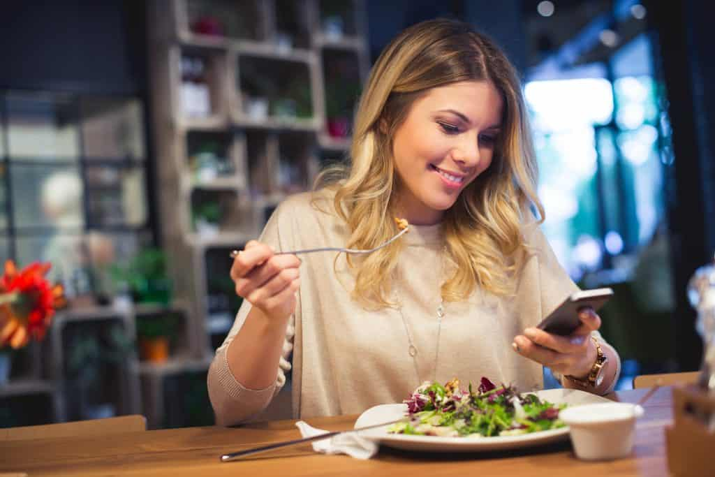 woman checking her phone while eating